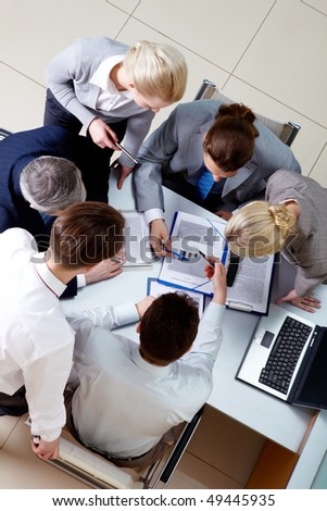 Above view of confident business partners interacting at meeting - stock photo