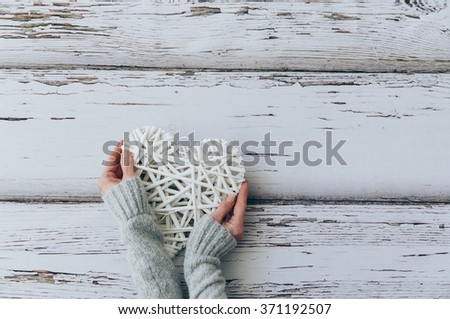 Above view of female hand holding  heart  on wood table. - stock photo