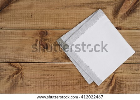 Above view of folded linen napking on wooden texture background - stock photo