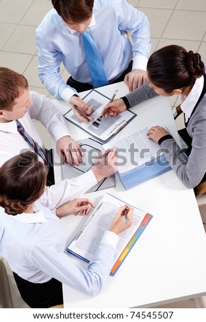 Above view of four businesspeople working businesspeople - stock photo