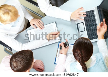 Above view of four businesswomen sitting at table and looking at the laptop screen - stock photo