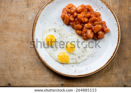 Above view of fried quail eggs with beans, studio shot - stock photo