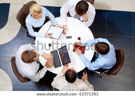 Above view of friendly businessteam working together at meeting - stock photo