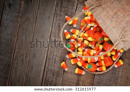 Above view of Halloween candy corn spilling from a burlap bag on rustic wood board background with room or space for copy, text, your words.  Horizontal that works vertical with Moody, dark vignette - stock photo