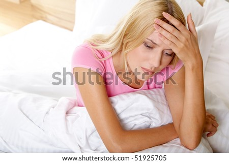 Above view of ill woman in bed touching her head - stock photo