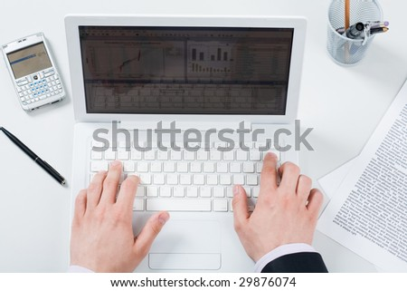 Above view of male hands pushing buttons of laptop with smartphone and papers near by - stock photo