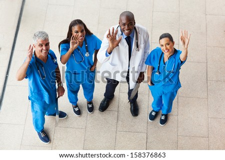 above view of medical doctors looking up and waving - stock photo