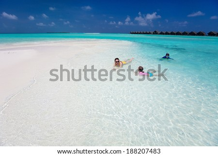 Above view of mother and kids enjoying tropical beach vacation - stock photo