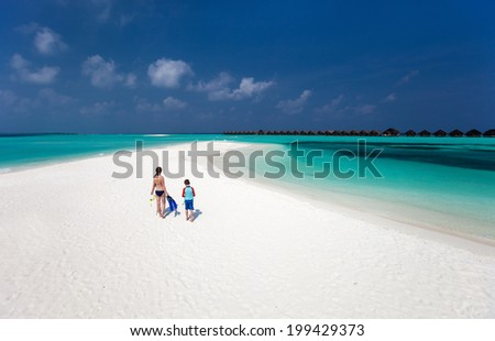 Above view of  mother and son walking at tropical beach with snorkeling equipment - stock photo