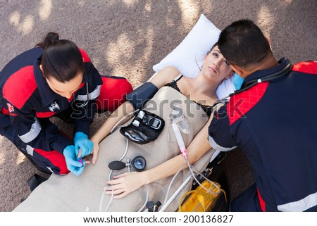 above view of paramedic team examining patient - stock photo