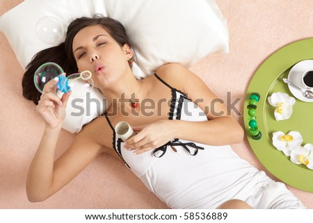 Above view of pretty girl blowing soap bubbles while lying on bed - stock photo