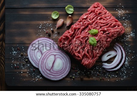 Above view of raw beef mincemeat with seasonings, studio shot - stock photo