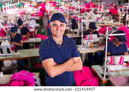 above view of senior clothing factory supervisor with arms crossed - stock photo