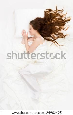 Above view of sleeping woman under white satin sheet - stock photo