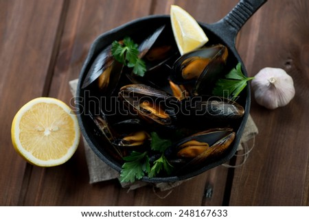 Above view of steamed mussels with parsley, lemon and garlic, studio shot - stock photo