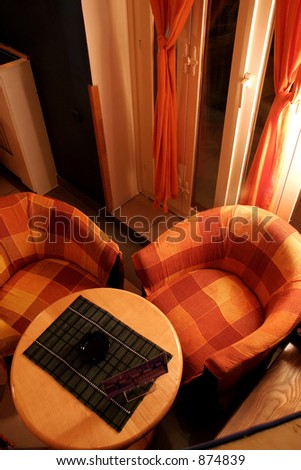 Above view of table and two chairs in a coffe shop. Dim lights. - stock photo