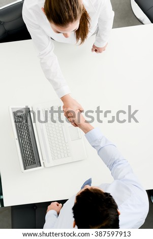 above view of two business people handshake with agreement contract in office - stock photo