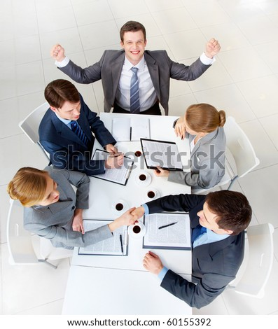 Above view of two business people handshaking while man near by showing his gladness - stock photo