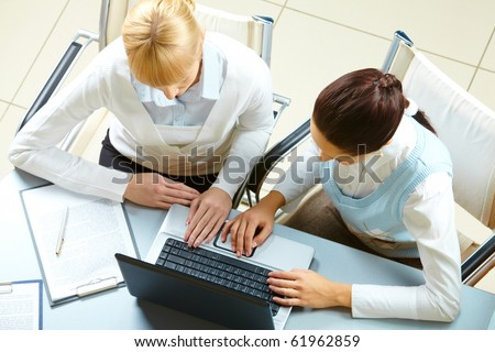 Above view of two businesswomen typing on a laptop - stock photo