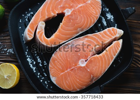 Above view of two fresh salmon steaks with sea salt, close-up - stock photo