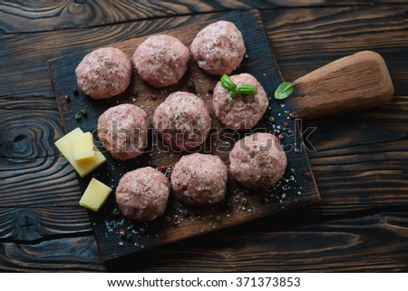 Above view of uncooked meatballs in a dark rustic wooden setting - stock photo