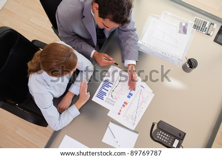 Above view of young business people talking about diagram - stock photo