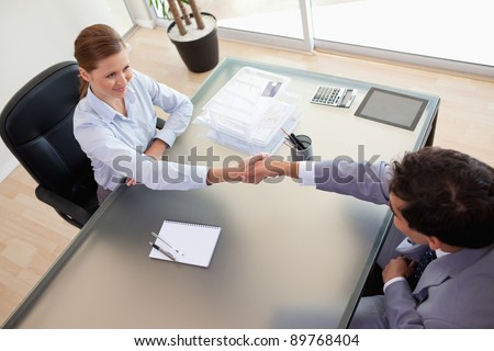 Above view of young consultant shaking hands with her client - stock photo