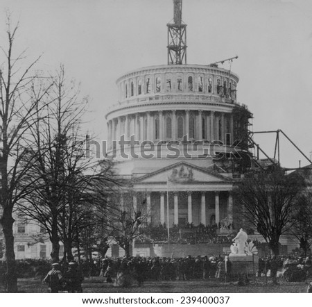 Abraham Lincoln's first inauguration on March 4, 1861 with crowds surrounding U.S. Capitol, which is under construction. - stock photo