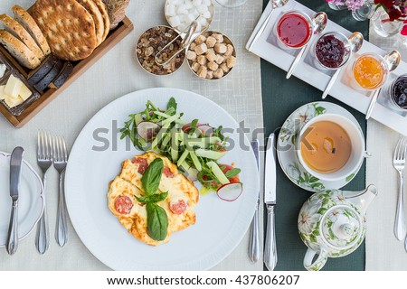 Absolutely Amazing Top View of Bread, Tea, Tasty Berry Jam, Scrambled Eggs with Salad on the Table for Breakfast, Brunch Time in Restaurant, Breakfast Conception - stock photo