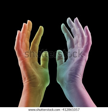Absorbing Color Light Therapy - Female hands reaching up with colored light projected onto skin in rainbow range of colors - red orange, yellow, green blue, magenta, against a black background  - stock photo