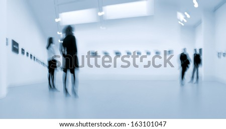 abstakt image of people in the lobby of a modern art center with a blurred background and a blue tonality - stock photo