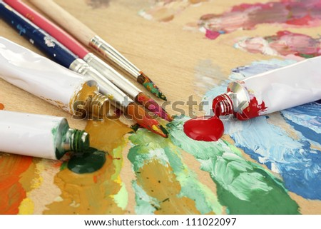 Abstract acrylic paint, paint tubes and brushes on wooden  palette - stock photo