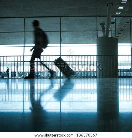 abstract airport and silhouette of walking person with luggage, commuter - stock photo