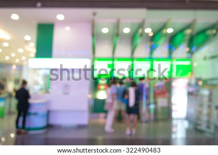 Abstract automatic teller machine ; ATM in front of the bank blurred background with bokeh in shopping mall. - stock photo