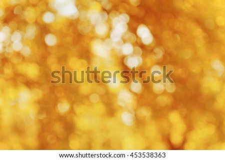 Abstract autumn bokeh background in yellow color. Blurred fall leaves. - stock photo
