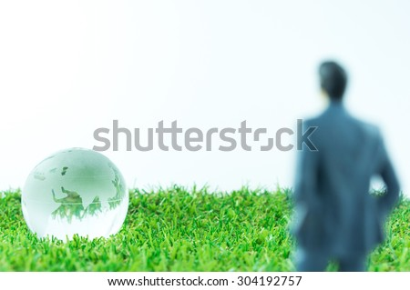 Abstract Background : Blur Miniature Business Man Looking To Glass Earth On Green Artificial Grass - stock photo