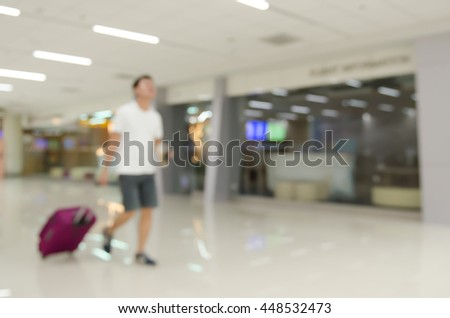 Abstract background,  blurred  image of a passenger with baggage walking in passenger terminal at the airport. - stock photo