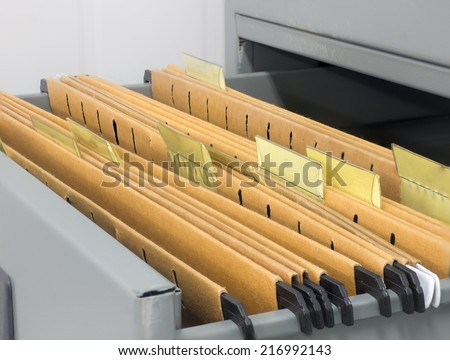 Abstract background image of colorful hanging file folders in drawer. Macro with with extremely shallow dof. Selective focus in front edges of files. - stock photo