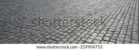Abstract background of old cobblestone pavement close-up. - stock photo
