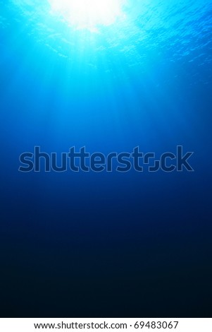 Abstract background of sunbeams in blue sea water - stock photo