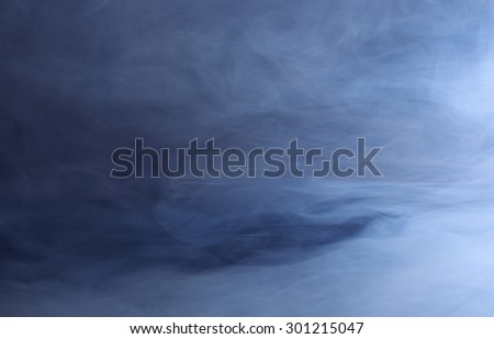 Abstract background of swirling blue smoke - stock photo