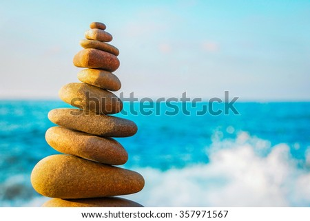 Abstract background. Stone tower on a pebble beach - stock photo