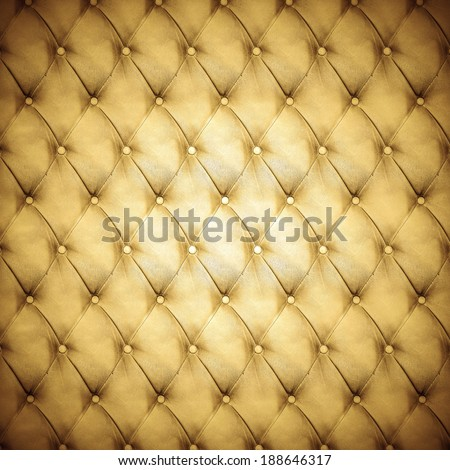 Abstract background texture of an old natural luxury, modern style leather with rhombs. Classic gold, black and dark brown grungy skin of retro wall, door, sofa or studio interior with metal buttons. - stock photo