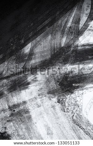 Abstract background texture of asphalt road covered with snow and tire tracks - stock photo
