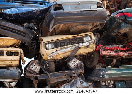 Abstract background with colorful dump of stacked cars in junkyard - stock photo