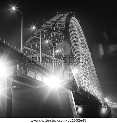 Abstract black and white photo. Traffic on night bridge. - stock photo