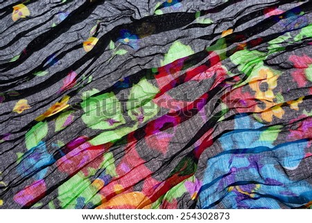 Abstract Black Background Wavy Folded Textured Fabric or Material  or Cloth Background With Floral Pattern - stock photo