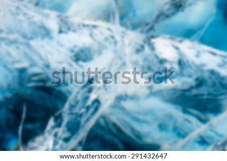 Abstract Blue river ice with large cracks. - stock photo
