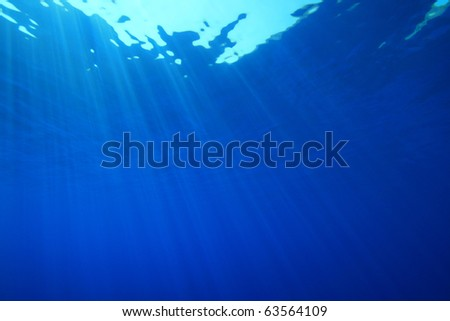 Abstract blue water background of sun rays in the ocean - stock photo