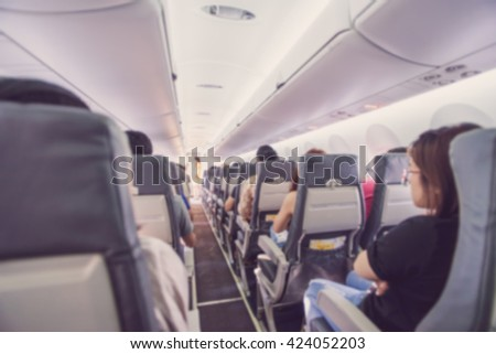 Abstract blur Interior of airplane with passengers on seats waiting to taik off. - stock photo